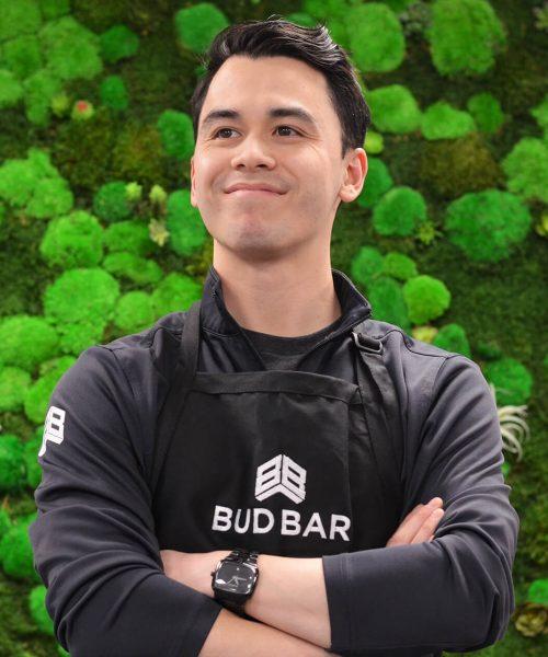 budbar-employee-posing-on-green-wall
